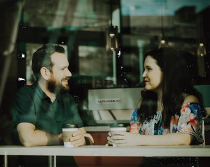 A man and woman facing each other in a coffee shop window - Relatives & Friends Programme Image