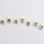 Wooden scrabble tiles are laid out to spell out anxiety
