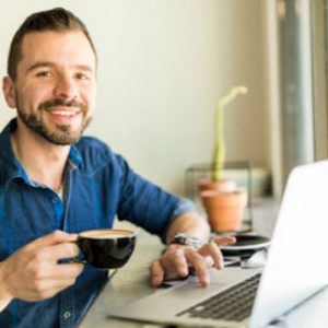 Man sitting at a laptop with a coffee - Life Skills Group Image